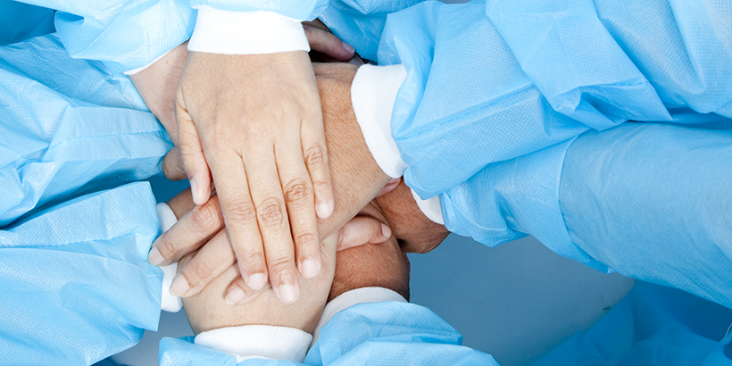Small group of doctor team joining hands